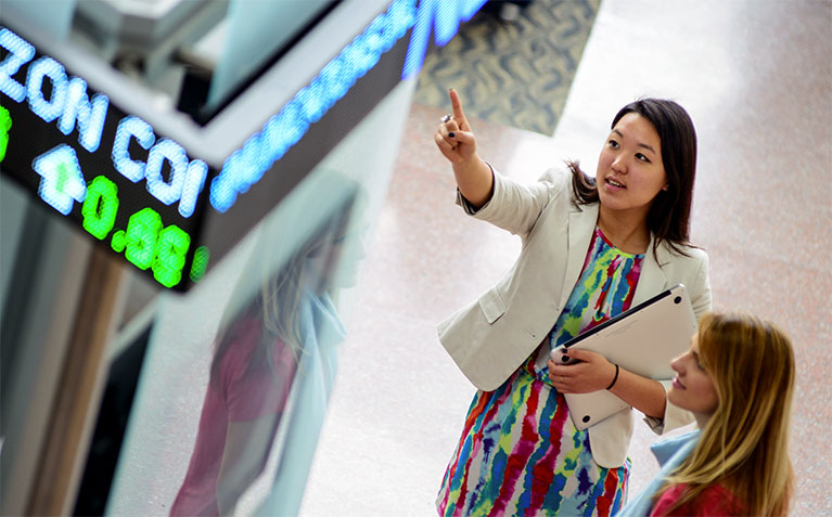 Schreyer Scholar Emily Zheng pointing at the ticker in the Smeal College of Business