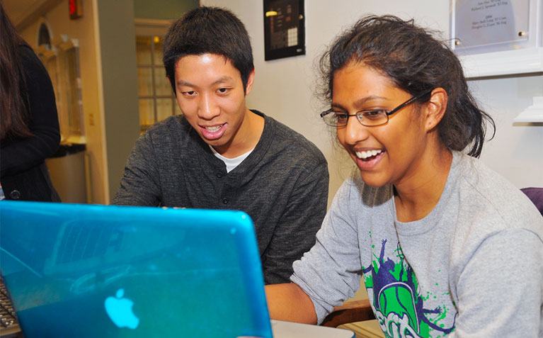 Two Scholars looking at a laptop